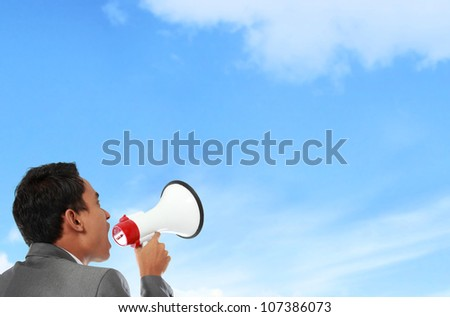 business man shouting using megaphone under the blue sky - stock photo