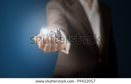 Business man showing a set of apartment on the hand - stock photo