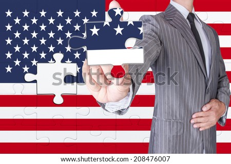 business man showing puzzle american flag part in business hand for complete nation - stock photo