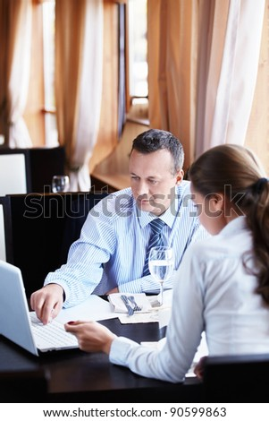 Business man shows a woman in a laptop - stock photo