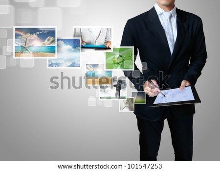 business man shows touch screen tablet with streaming images - stock photo