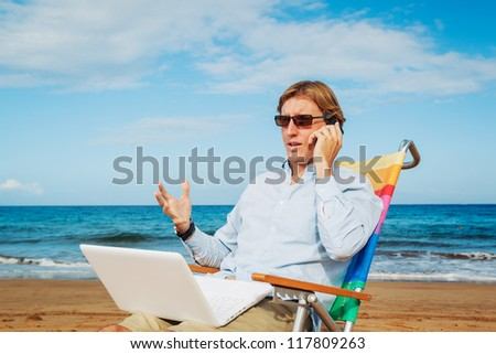 Business man sitting and working on the beach working on mobile computer - stock photo