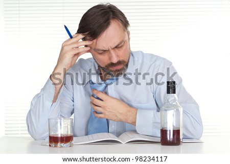 Business man sitting at a table with a bottle on a light background - stock photo