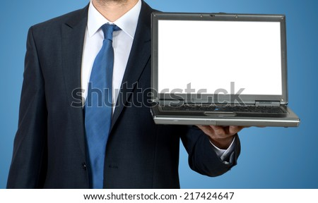 Business man sitting at office desk with laptop computer facing the camera and showing you something on laptop - stock photo