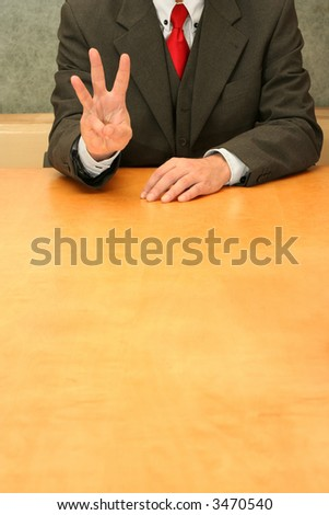 Business-man sitting at the desk, fingers indicating number three. - stock photo