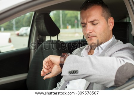 business man sitting in a car and looking at his watch - stock photo