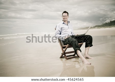 business man sitting on a chair on the beach with laptop. warm tinted image with sepia. - stock photo