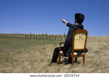 Business man sitting on a chair on the meadow pointing to the blue sky - stock photo