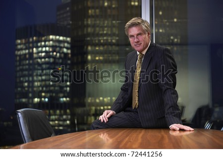 Business man sitting on table in boardroom looking at camera - stock photo