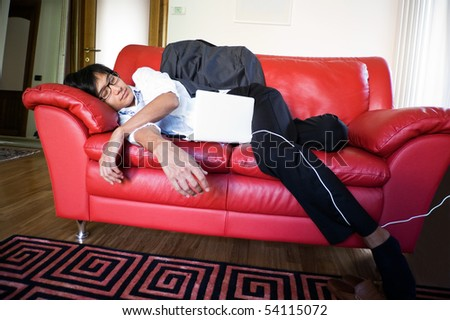 business man sleeping on the sofa with a white laptop - stock photo