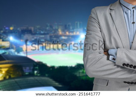 Business man sport manager and executive with background of soccer ball athletic stadium and race track - stock photo