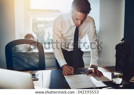 Business man standing at desk working on documents, white shirt and tie, male executive - stock photo