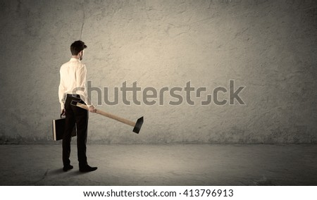 Business man standing in front of a grungy copyspace wall with a hammer - stock photo