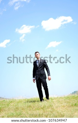 Business man standing in nature - stock photo
