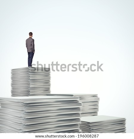 Business man standing on a pile of blank documents - stock photo