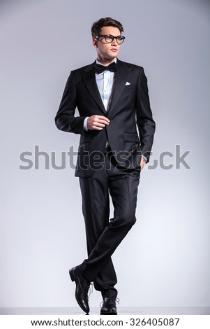 Business man standing on studio background with his legs crossed while opening his jacket. - stock photo