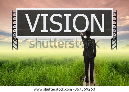 business man standing on wood bridge between rice field and pointing with large sign of vision (business concept) - stock photo