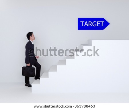 Business man stepping up on stairs to business target - stock photo