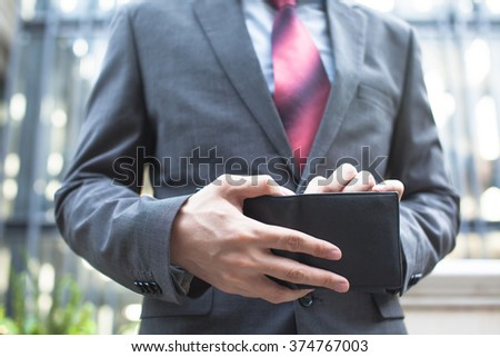 Business man taking bills out of wallet - stock photo
