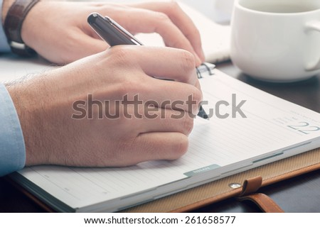 Business man taking notes at the meeting - stock photo