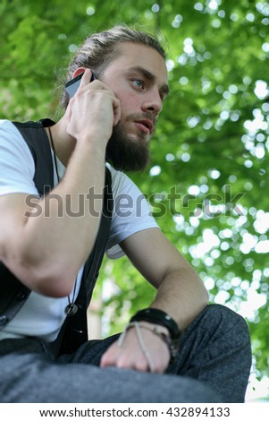 Business man talking on smart phone in the park. View from below.  Green business. - stock photo
