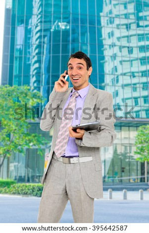 Business man talking on the phone and holding a tablet outdoors over city background  - stock photo