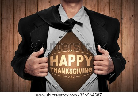 Business man tears open his shirt in a super hero fashion with happy thanksgiving writing - stock photo