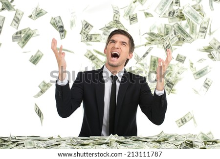 Business man throwing dollar bills and yelling. Young businessman sitting with money in office - stock photo