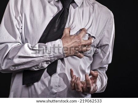 Business man thumbs up with a cramped hand to his heart: He has a heart attack. - stock photo