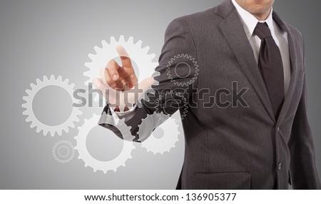 business man touching gear on glass board - stock photo
