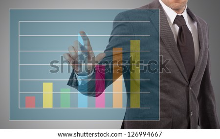business man touching graph on screen, grey background - stock photo
