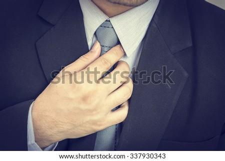 business man touching his tie. Close up,Closeup portrait of businessman in blue collar shirt and suit with tie,selective focus. - stock photo