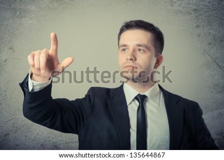 business man touching virtual screen, grey background - stock photo