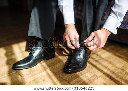 Business man tying shoe laces on the floor. Close-up. - stock photo