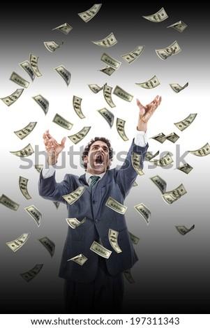 business man under falling money banknotes screaming reaching for it, dollar rain, stressed man grabbing falling money - stock photo