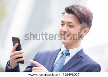 Business man use smart phone with business office building background, asian - stock photo