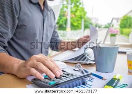 business man using a calculator to calculate the numbers on his desk. - stock photo
