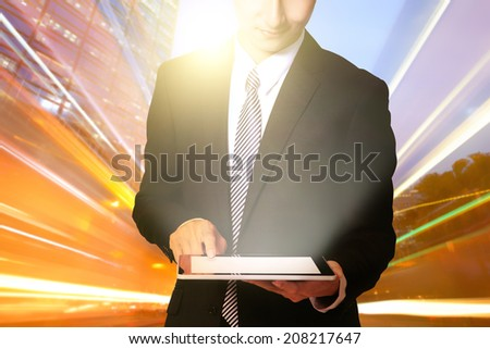 business man using digital tablet with city traffic light trail at night, asia, china, hong kong - stock photo