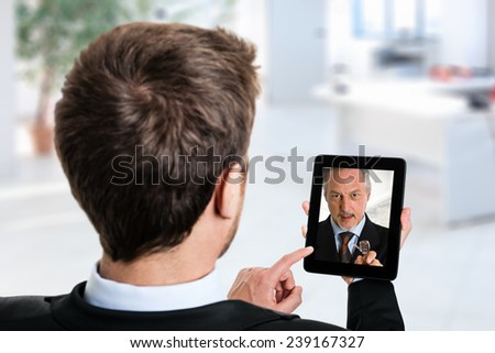 Business man using his tablet to speak to a colleague - stock photo