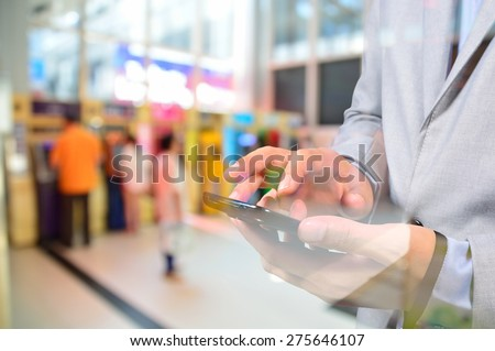 Business Man using Mobile Digital smartphone in Business Center as Online Financial activity or Mobile Banking concept with ATM Background.  Double Exposure effect applied. - stock photo