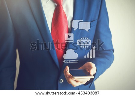 Business man using smart phone with internet icons floating off the screen - stock photo