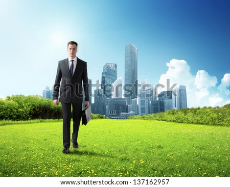 business man walking on green field and modern city - stock photo