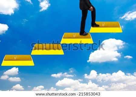 business man walking up gold bars stepping ladder on blue sky  idea concept step by step for success and growth business - stock photo