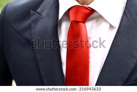Business man wearing a suit with a red tie. Detail on the tie. - stock photo