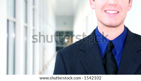 Business man wearing blue suit, blue shirt, and black tie is smiling in the middle of a white hallway - stock photo