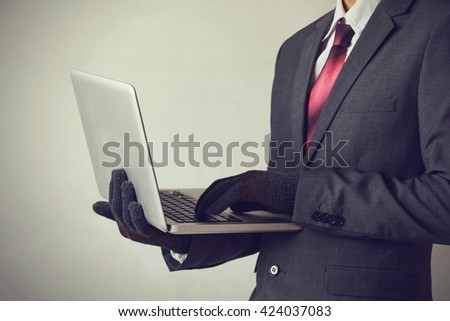 Business man wearing gloves and using computer - fraud, hacker, theft, cyber crime concept - stock photo
