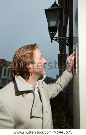Business man white coat long hair entering office building - stock photo