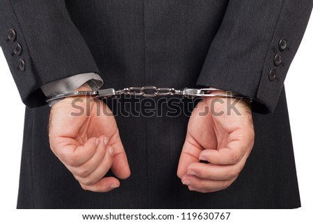 business man with a black suit in handcuffs, back view - stock photo