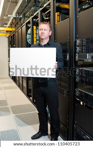 Business man with a contemplative look holding a white board in a datacenter. - stock photo