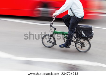 business man with a folding bike in the city traffic in motion blur - stock photo
